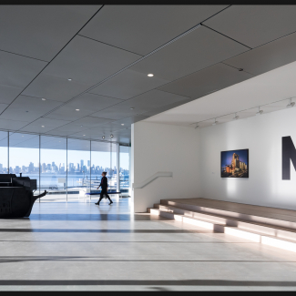 Photograph of Lobby with temporary exhibit and Vancouver skyline in background.