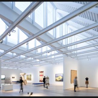 Photographie de la salle d'exposition principale du deuxième étage, avec les lanterneaux continus orientés vers le nord et les pannes pour l'électricité, l'éclairage, les supports médias, et les œuvres d'art accrochées.