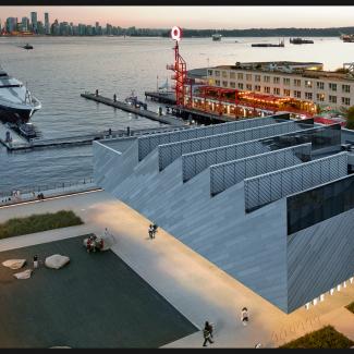 Photographie de l'ensemble du bâtiment avec le bassin public, la promenade de la digue, le quai Lonsdale, un bateau imposant, le Sea Bus, les transports en commun et la silhouette de Vancouver.