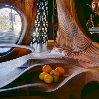 Le travail de menuiserie du Bar Raval définit l'espace et intègre des éléments fonctionnels tels que des comptoirs et un bol à fruits.