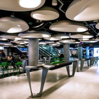 Intérieur de l'aire de restauration avec plafond en PODs conçu par PARTISANS. PARTISANS a également conçu les tables et les poubelles de l'aire de restauration.