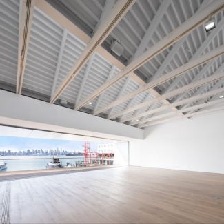 Photograph of Event Gallery with opened panoramic wall to exterior balcony and view to Vancouver Skyline across Burrard Inlet