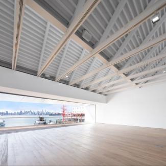 Photographie de la salle des événements comportant un mur panoramique ouvert sur le balcon extérieur et vue sur la silhouette de Vancouver de l'autre côté de Burrard Inlet